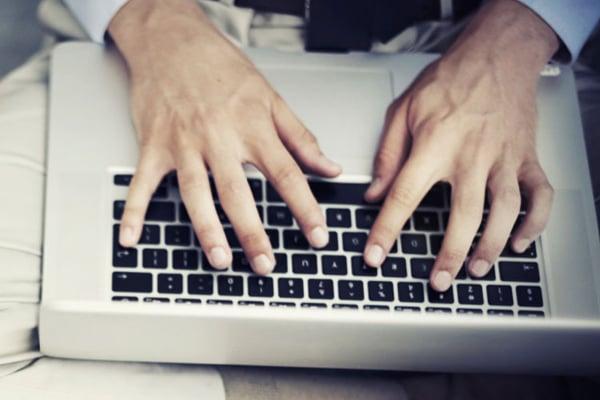 man-typing-on-apple-macbook-laptop-keyboard